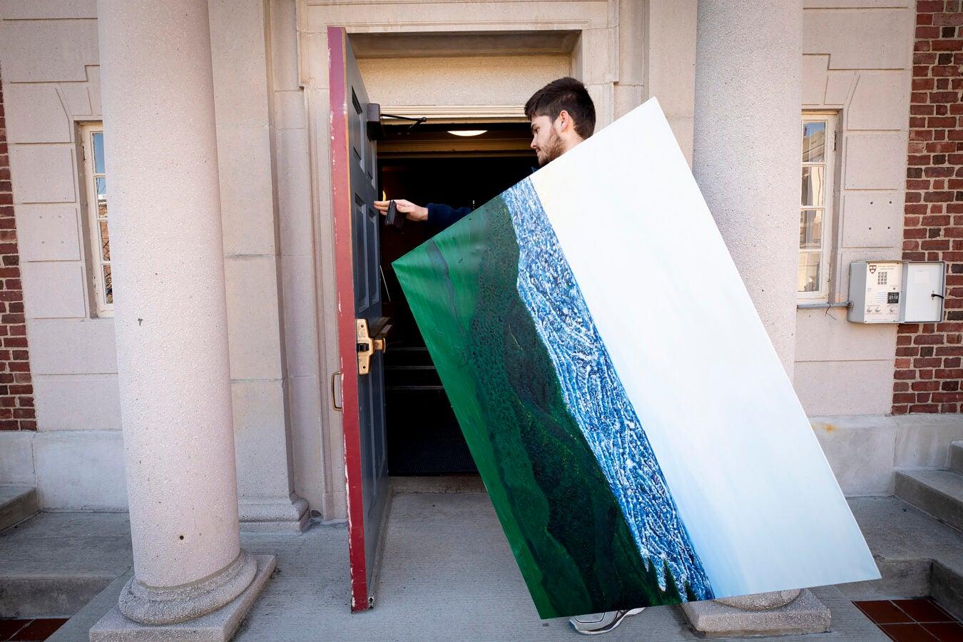 Rodrigo Cordova carries his painting.