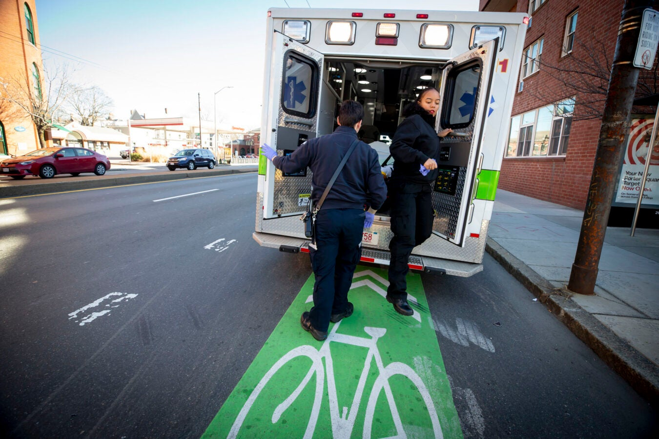 EMTs exit the back of an ambulance parked on the street.