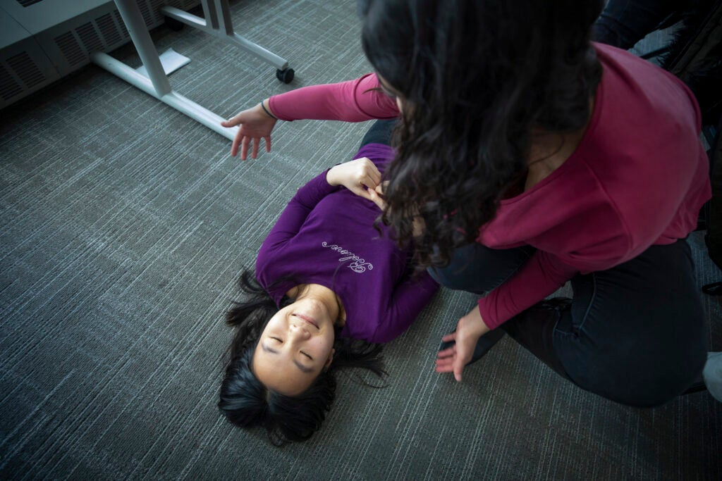 A student lies on the floor as another checks for bleeding.