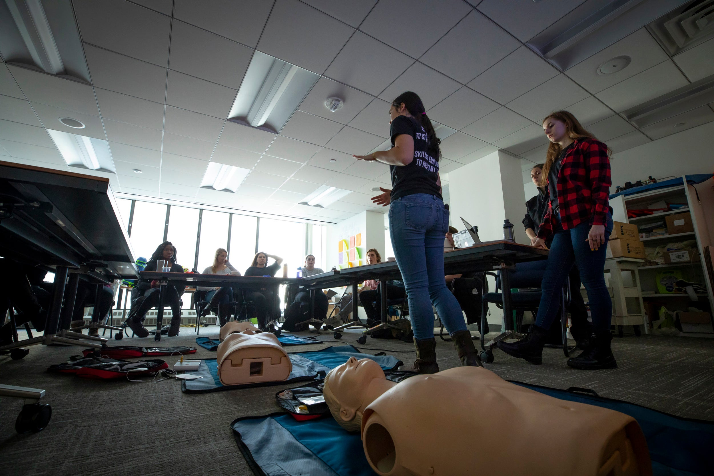 Students sit at desks in a CPR class.