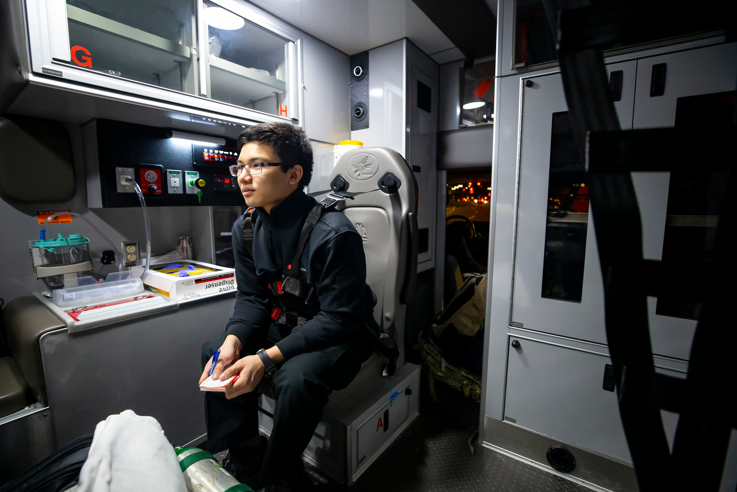 Benjamin Ho takes notes in the back of an ambulance.