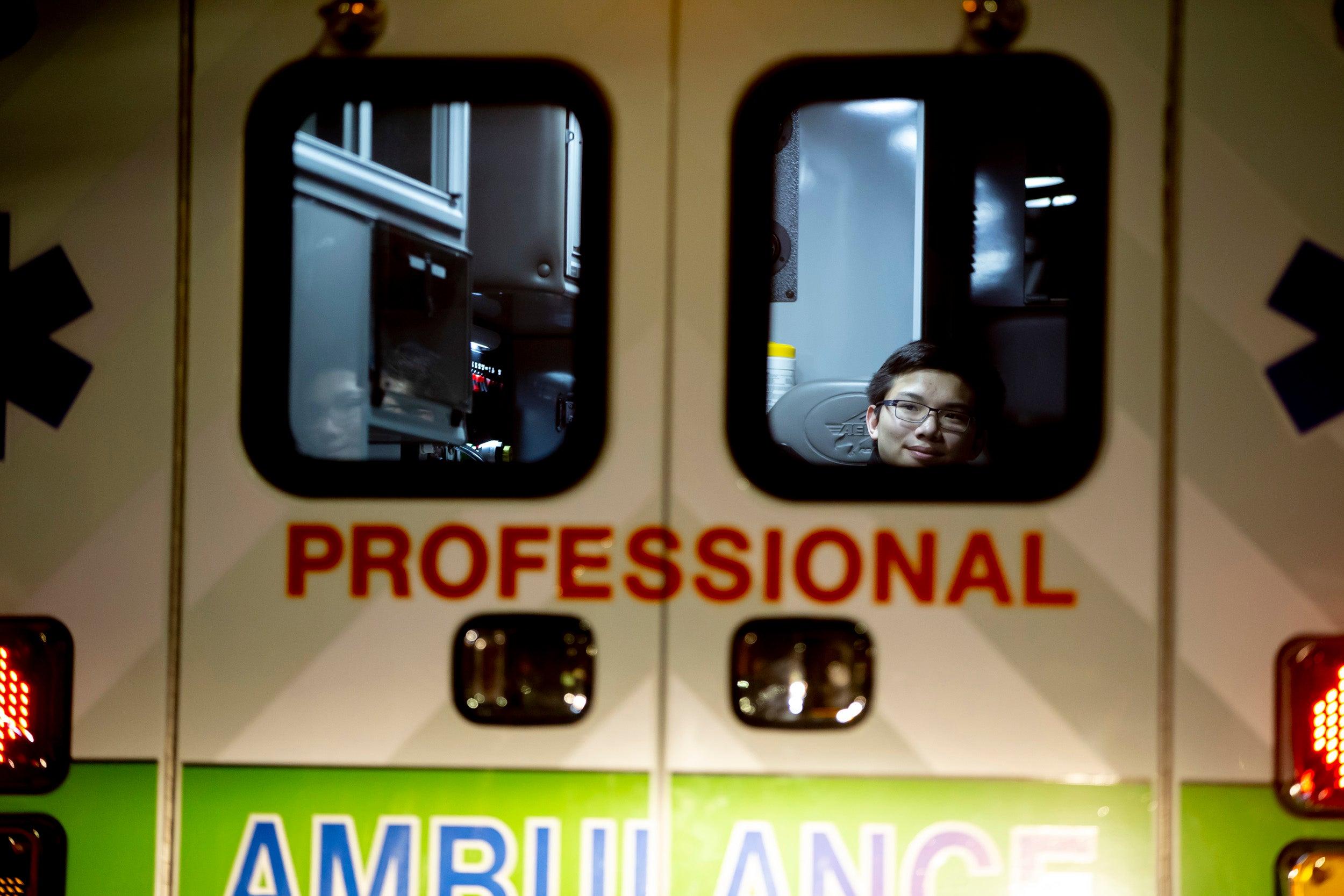 Benjamin Ho is seen through the back door of an ambulance.