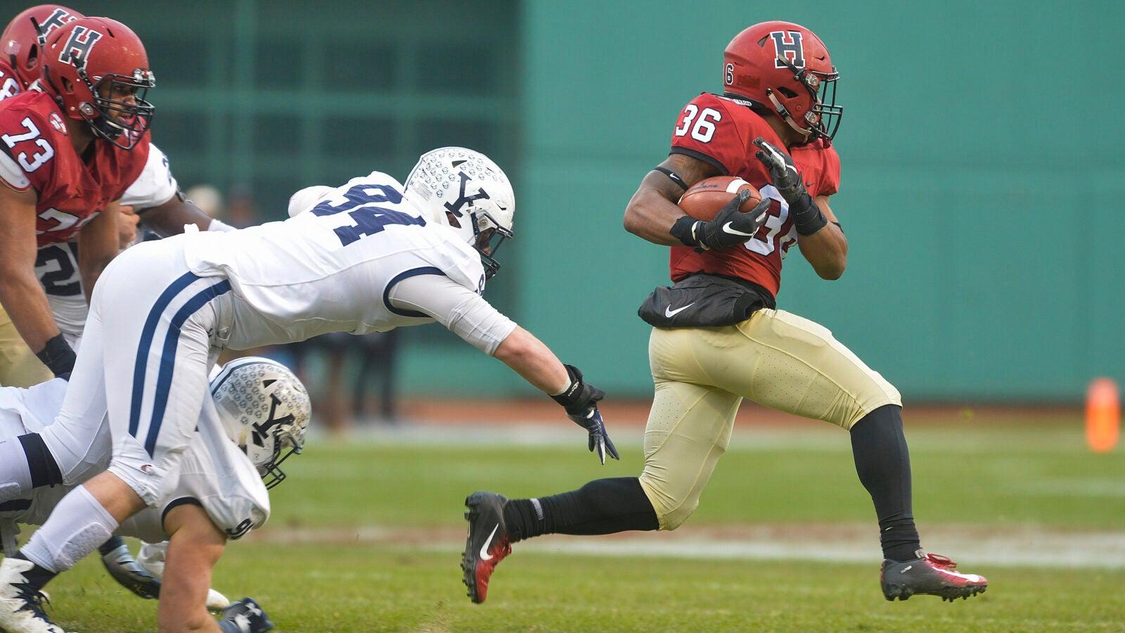 A Harvard football player running down the field