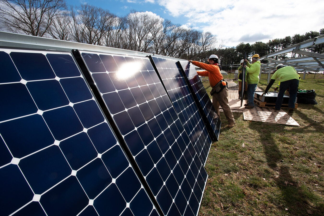 Construction workers erect solar panels