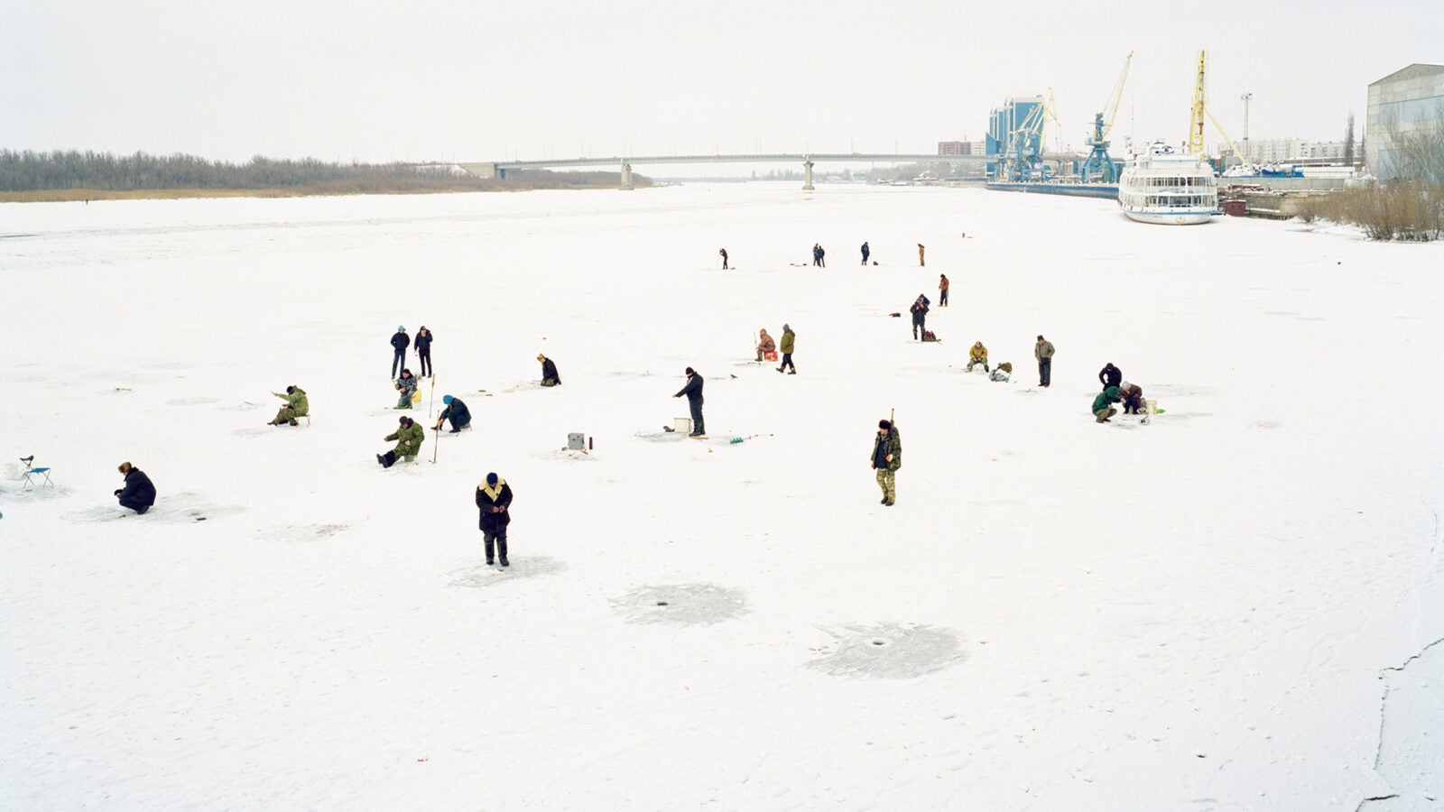 Fishermen cut holes in frozen river on the outskirts of the city, Astrakhan, Russia.