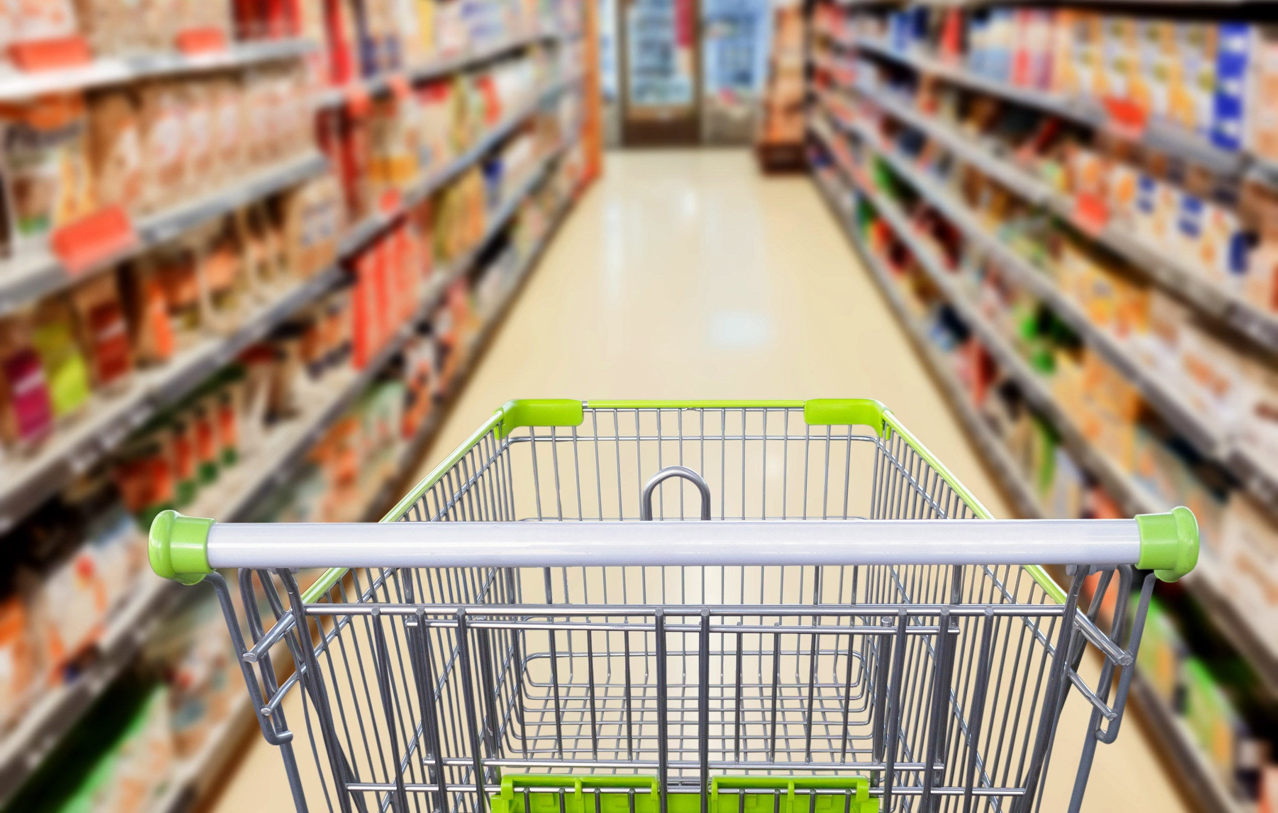 Supermarket aisle with empty shopping cart
