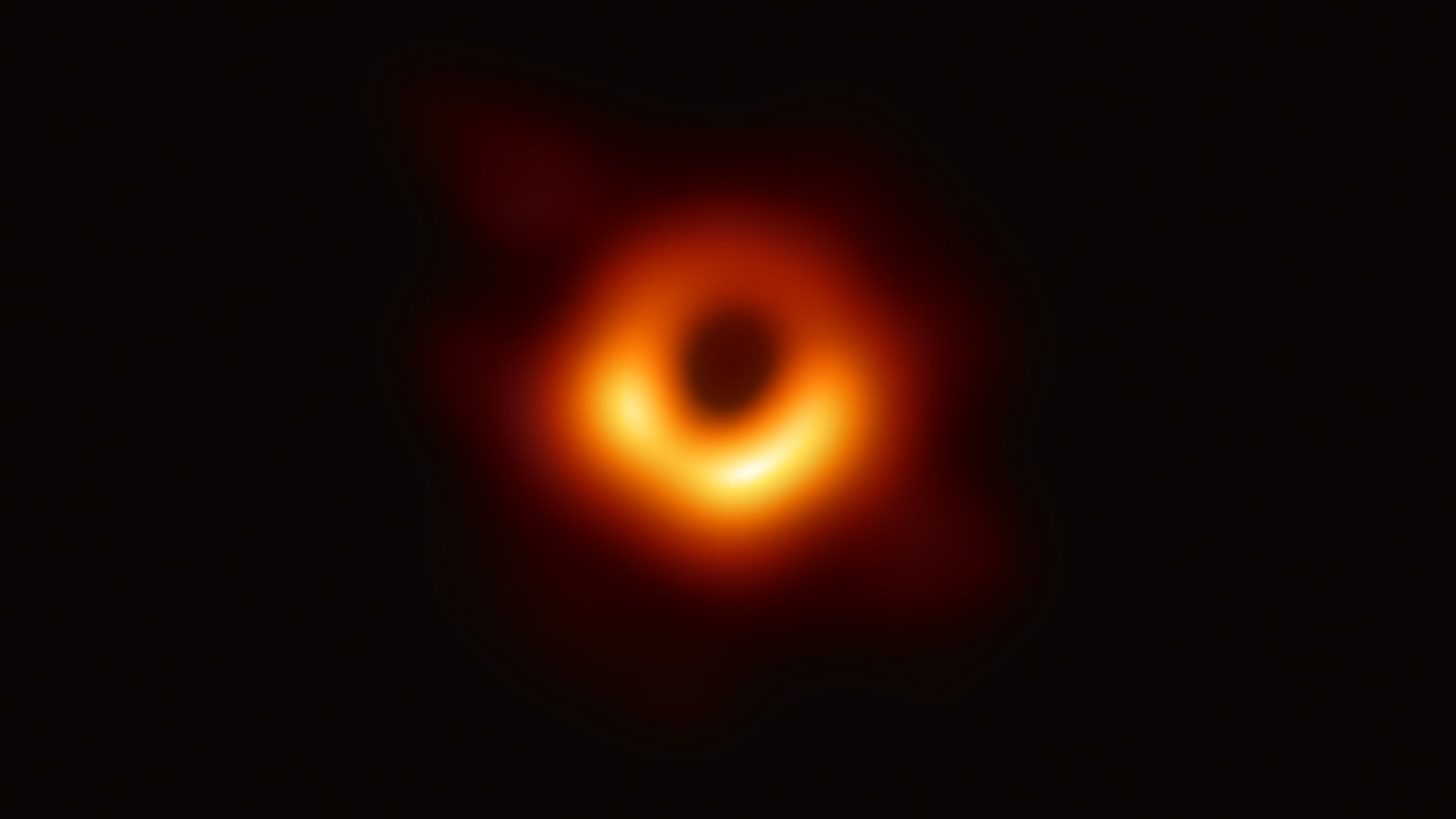 In the first picture of a black hole, it is outlined by emission from hot gas swirling around it under the influence of strong gravity near its event horizon.