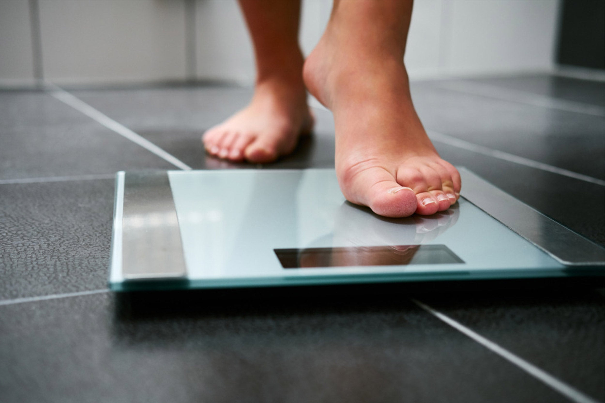 Person getting ready to weigh themselves on a scale.