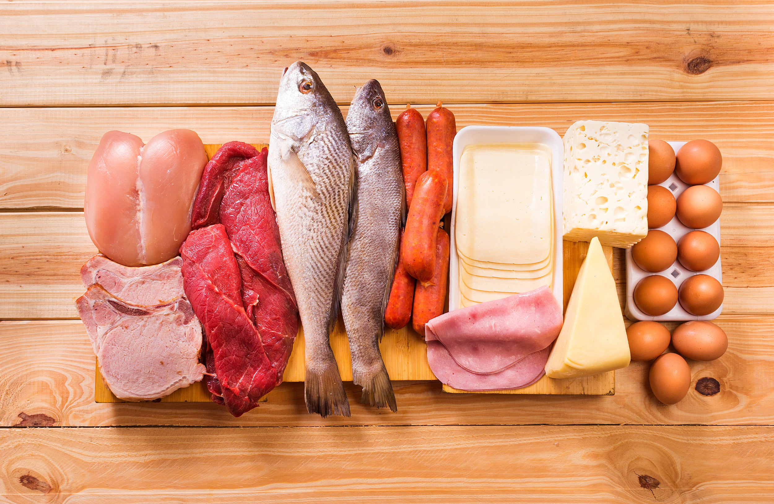 meats, fish, dairy, eggs, white meat on a wooden table as background