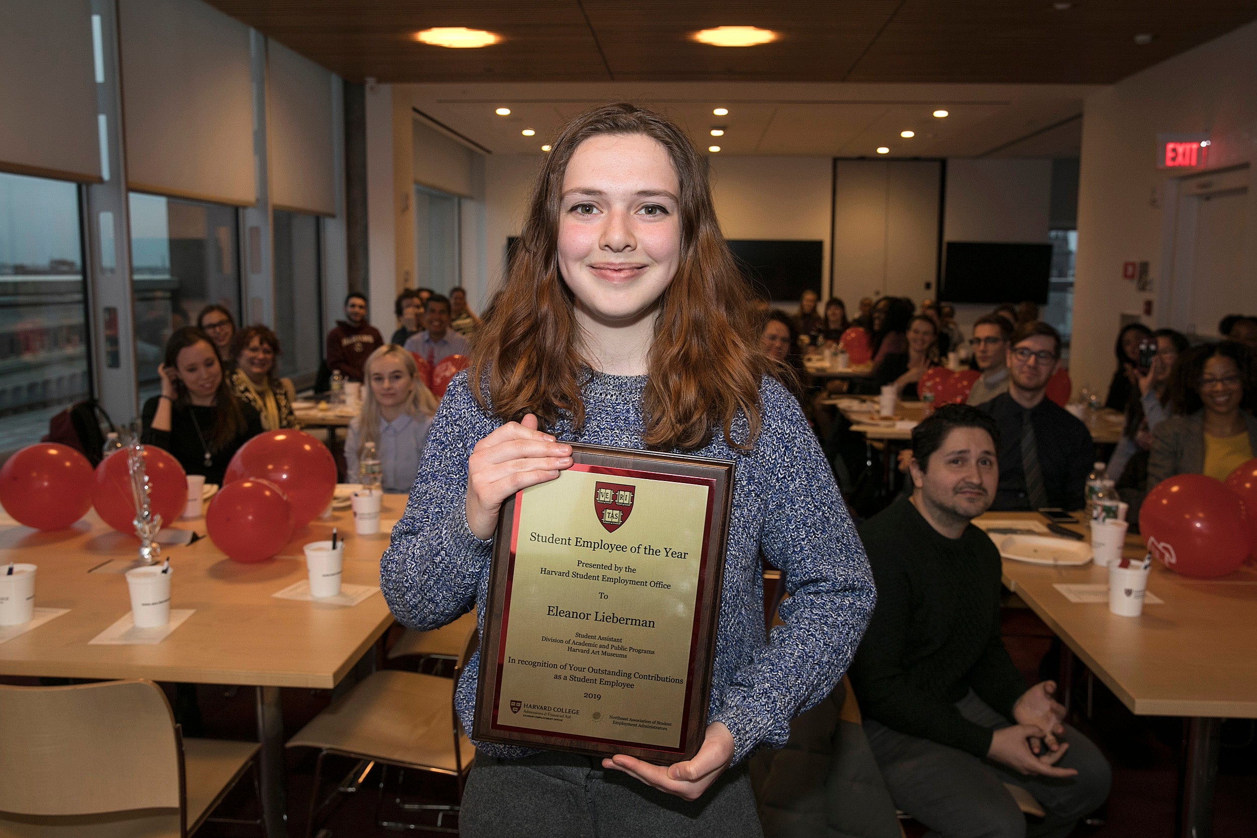 Eleanor Lieberman holds her Student Employee of the Year plaque