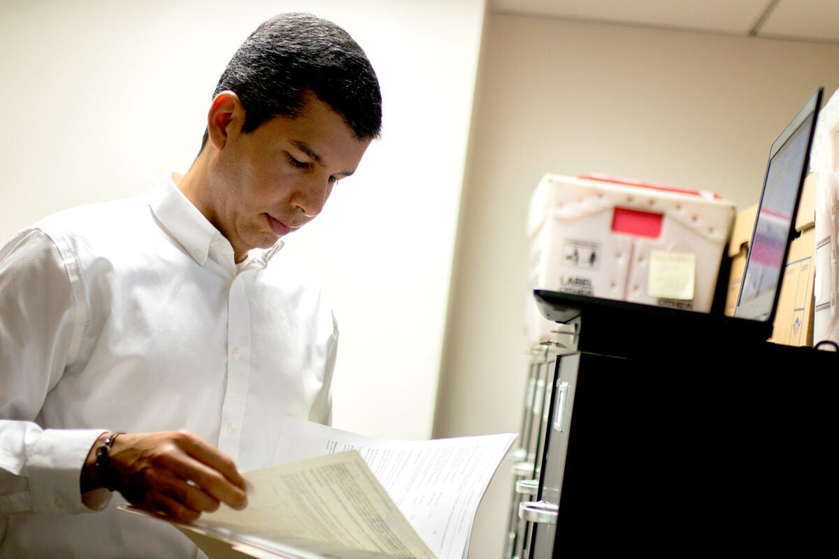Salvador Peña looks at a file in an office