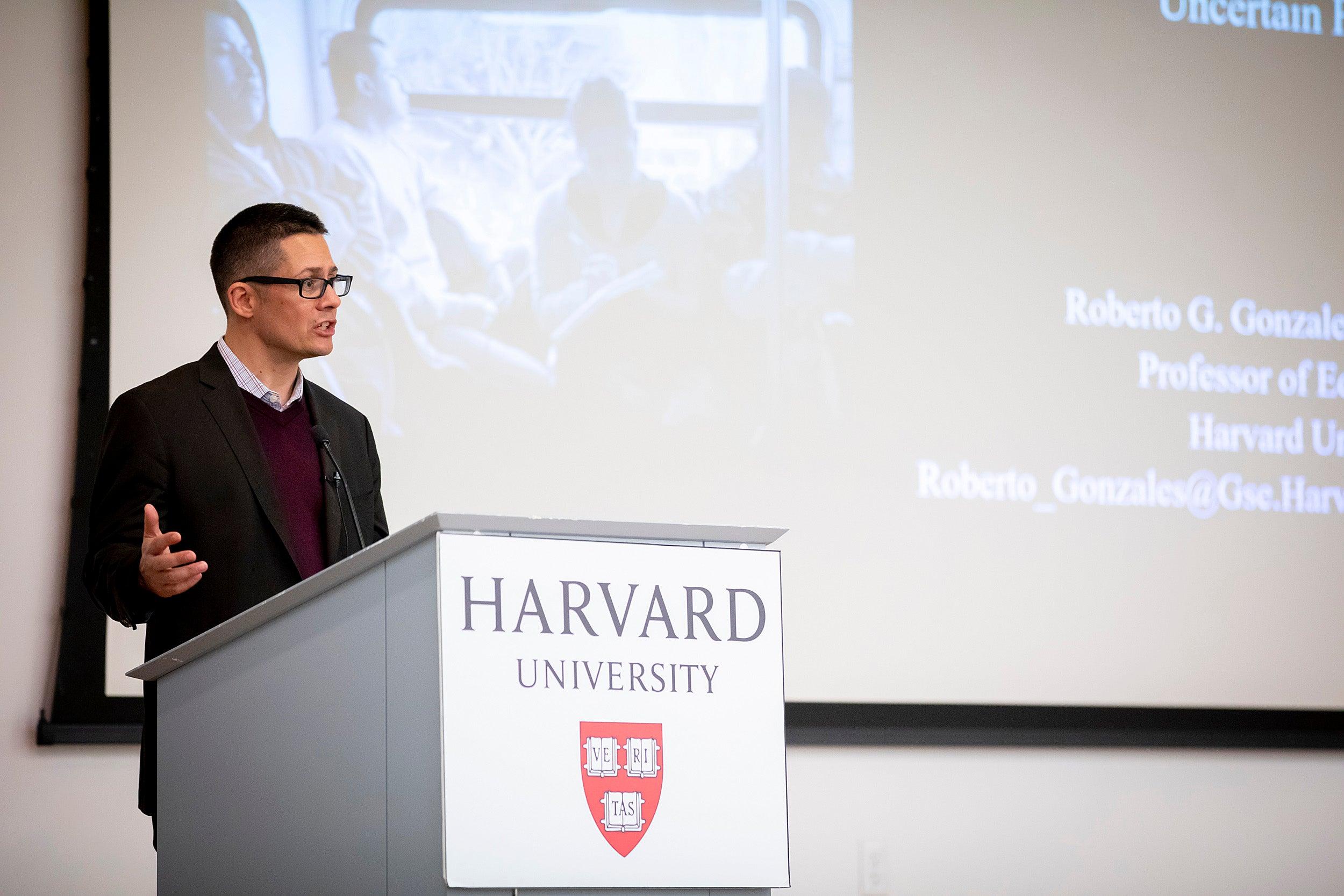 Roberto Gonzales gives presentation at podium.