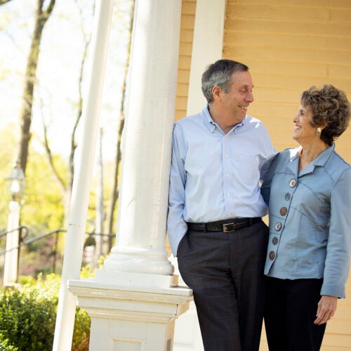 Larry and Adele Bacow standing on their porch of their Elmwood home.