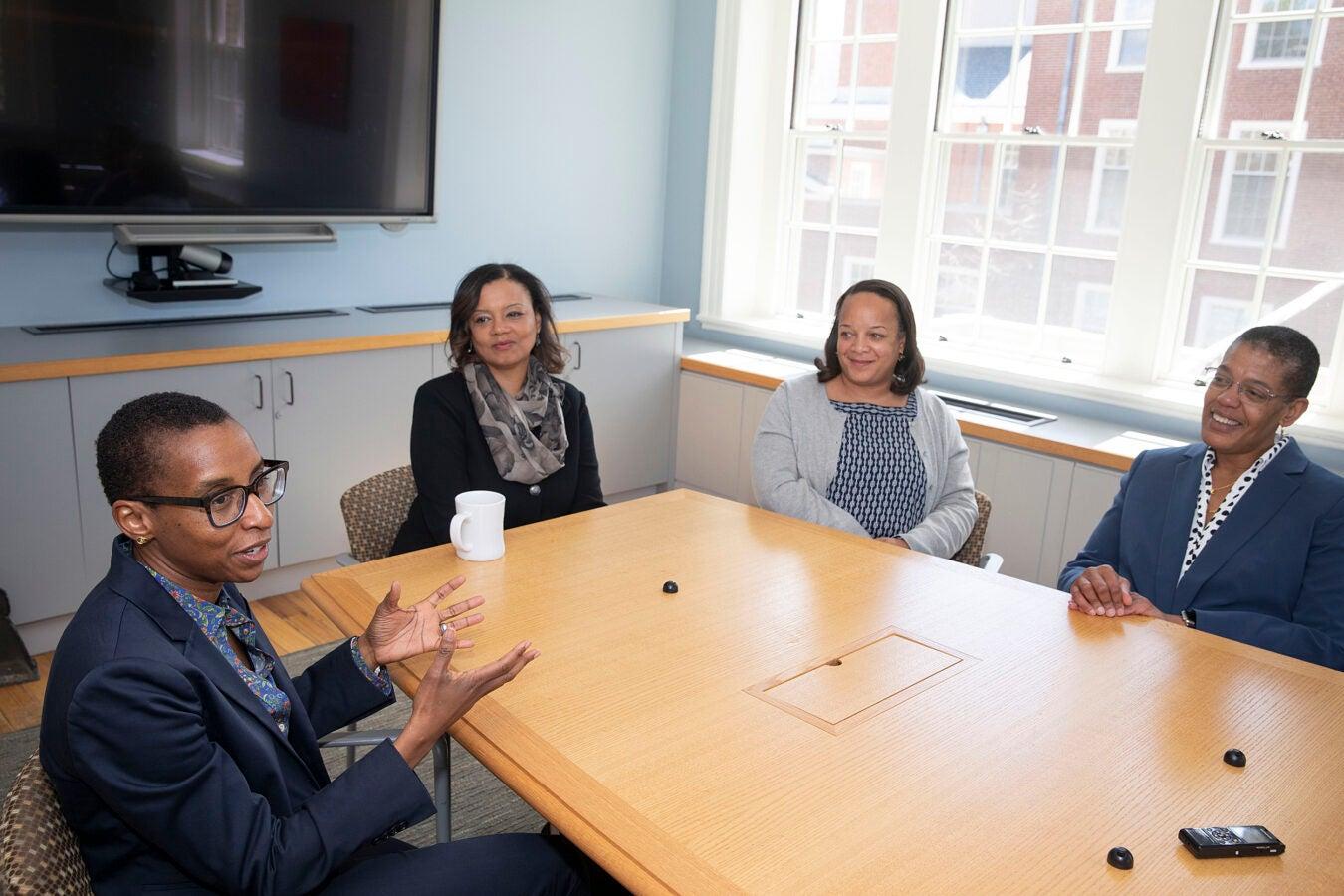 four women talking around a table
