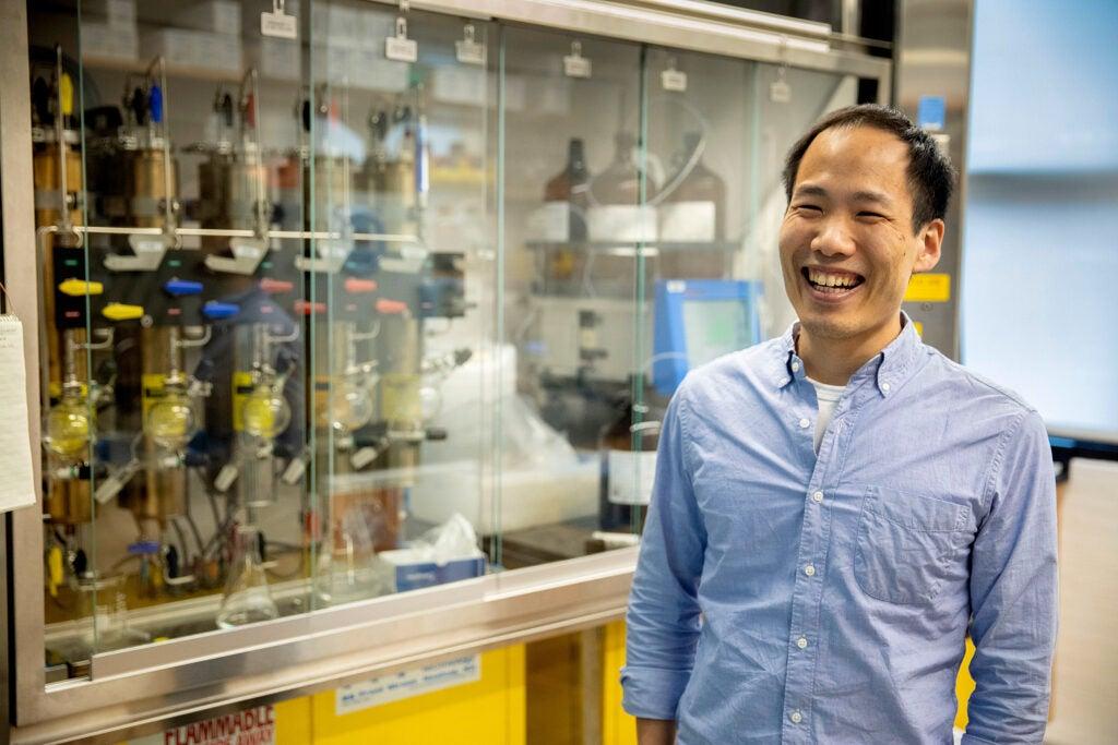 Professor smiles in front of lab equipment