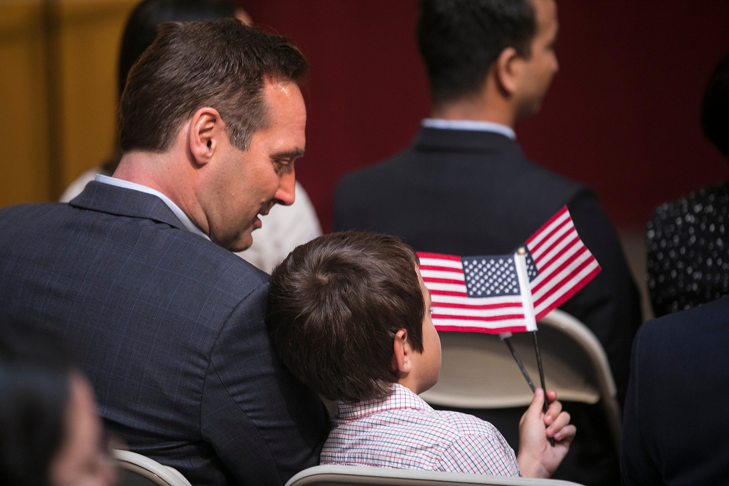man sitting with son, holding American flag