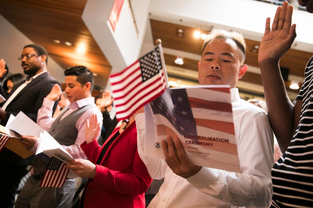 Man holding American flag reading from a booklet at a ceremony