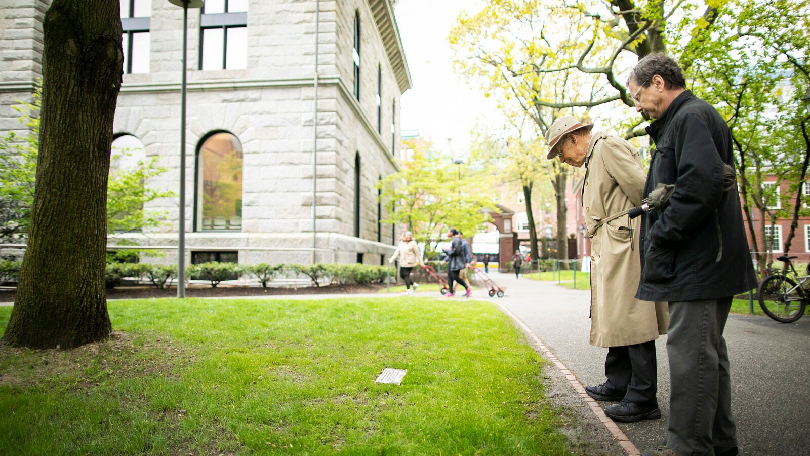 Two men examine plaque in Harvard Yard.