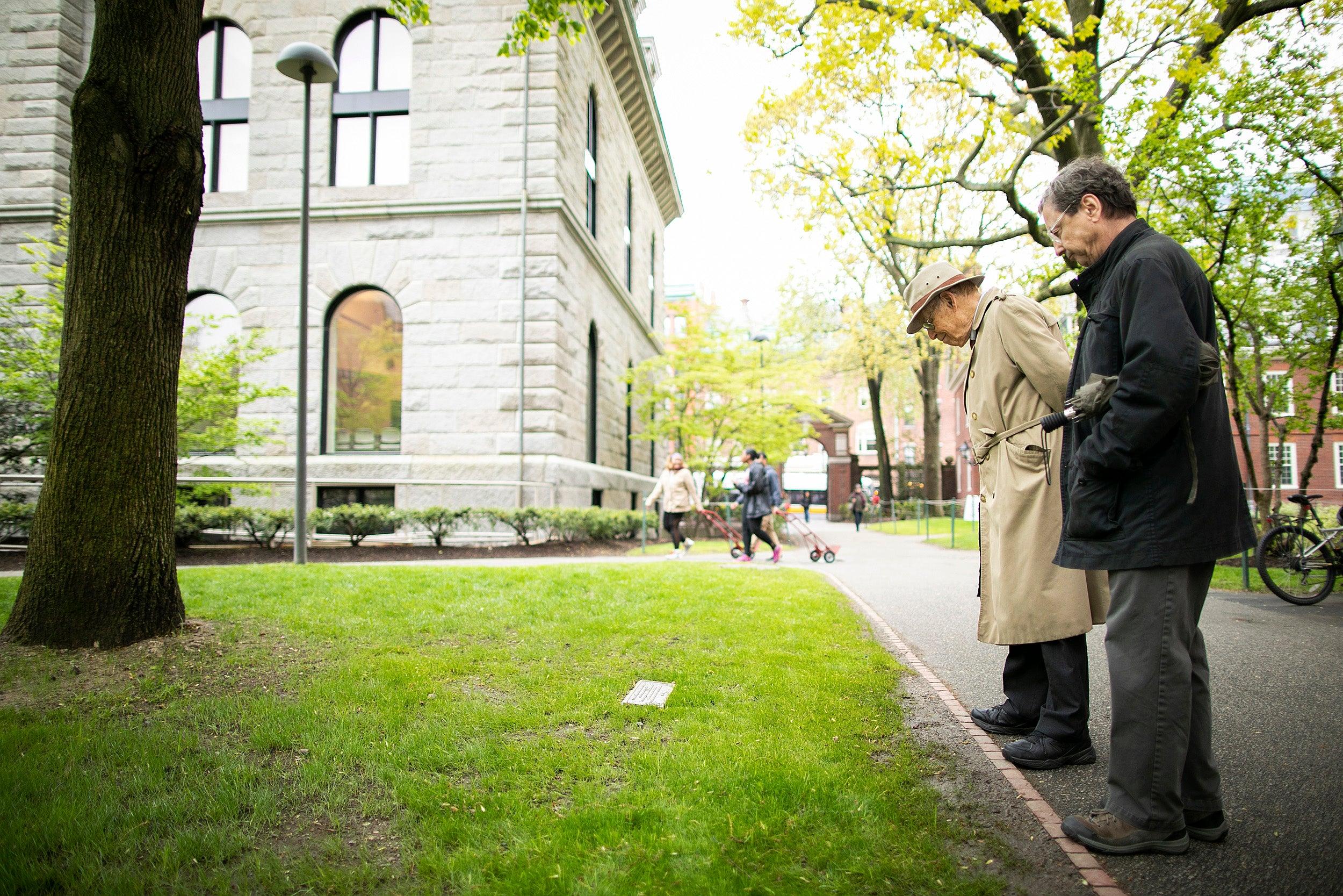 Two men examine plaque in Harvard Yard.