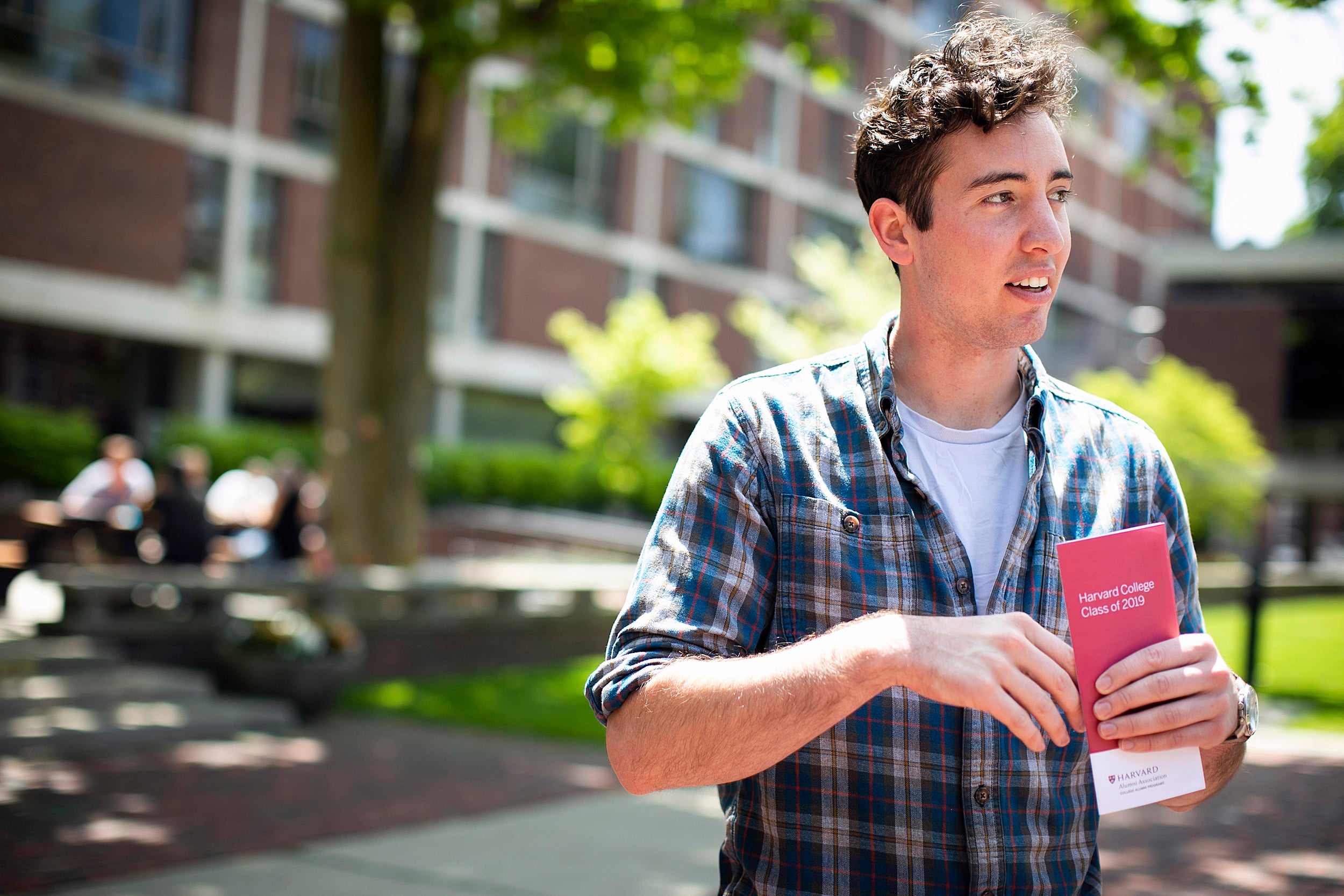 Jacob Link holds a Commencement brochure