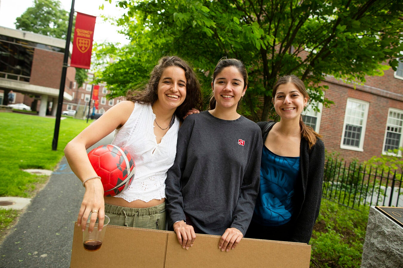 Three friends hold a cardboard poster in the Quincy House courtyard