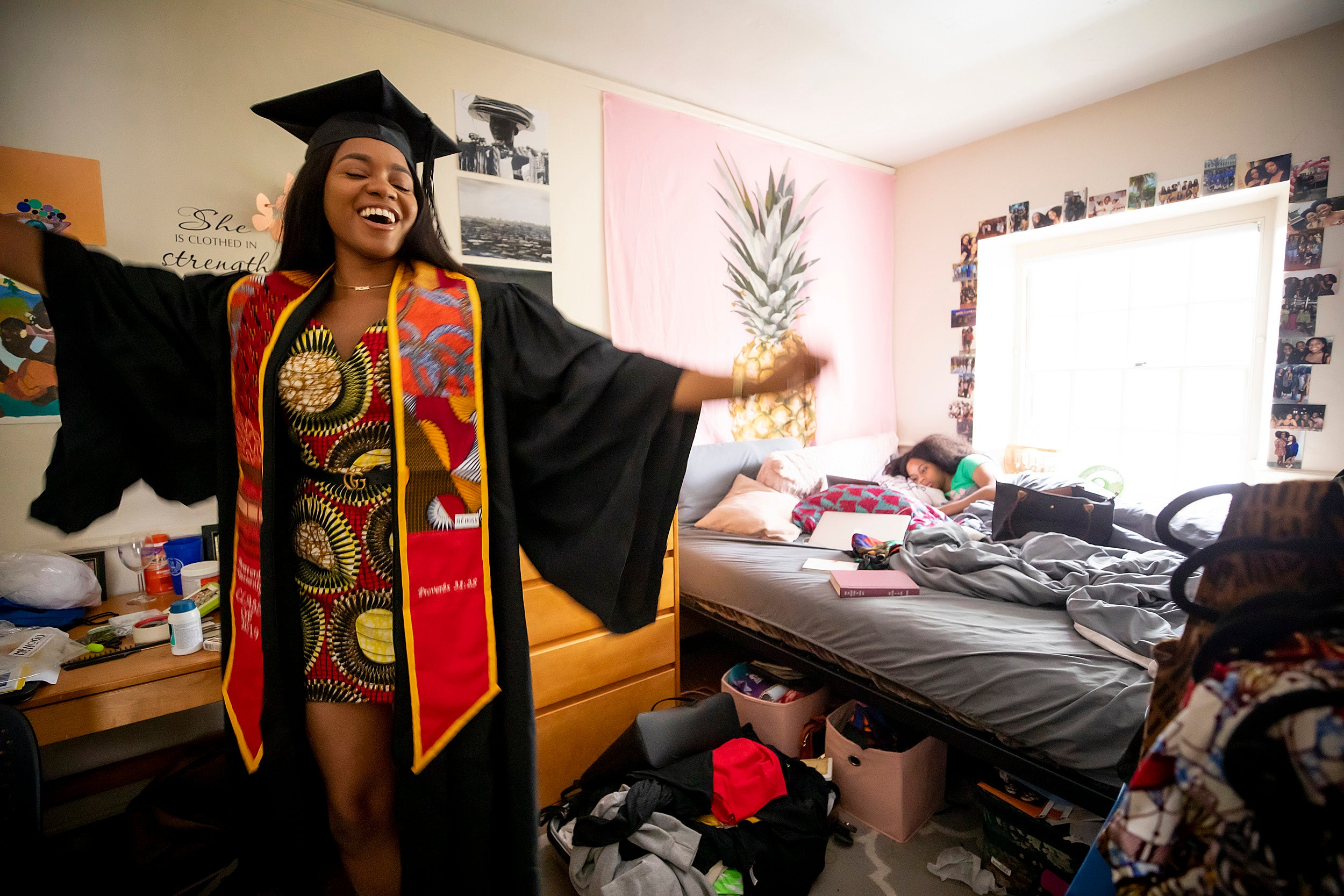 Angelica Chima dances in excitement in her Eliot House room before the ceremony while her visiting sister sleeps behind her.