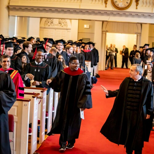 Larry Bacow and Jonathan Walton walk down the aisle of Memorial Church for the 2019 Baccalaureate Service.