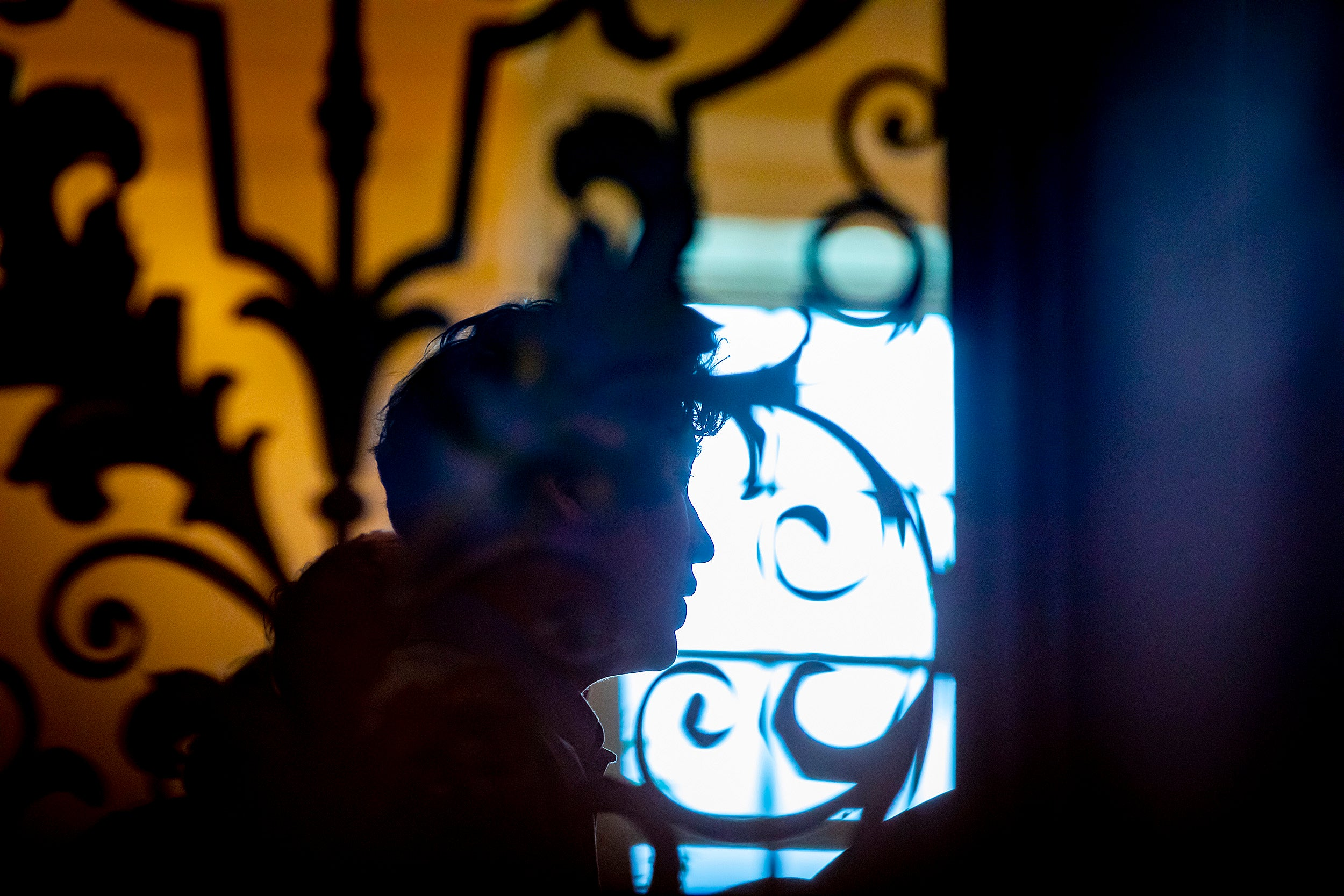 Silhouette of choir member framed by wrought iron in Memorial Church.