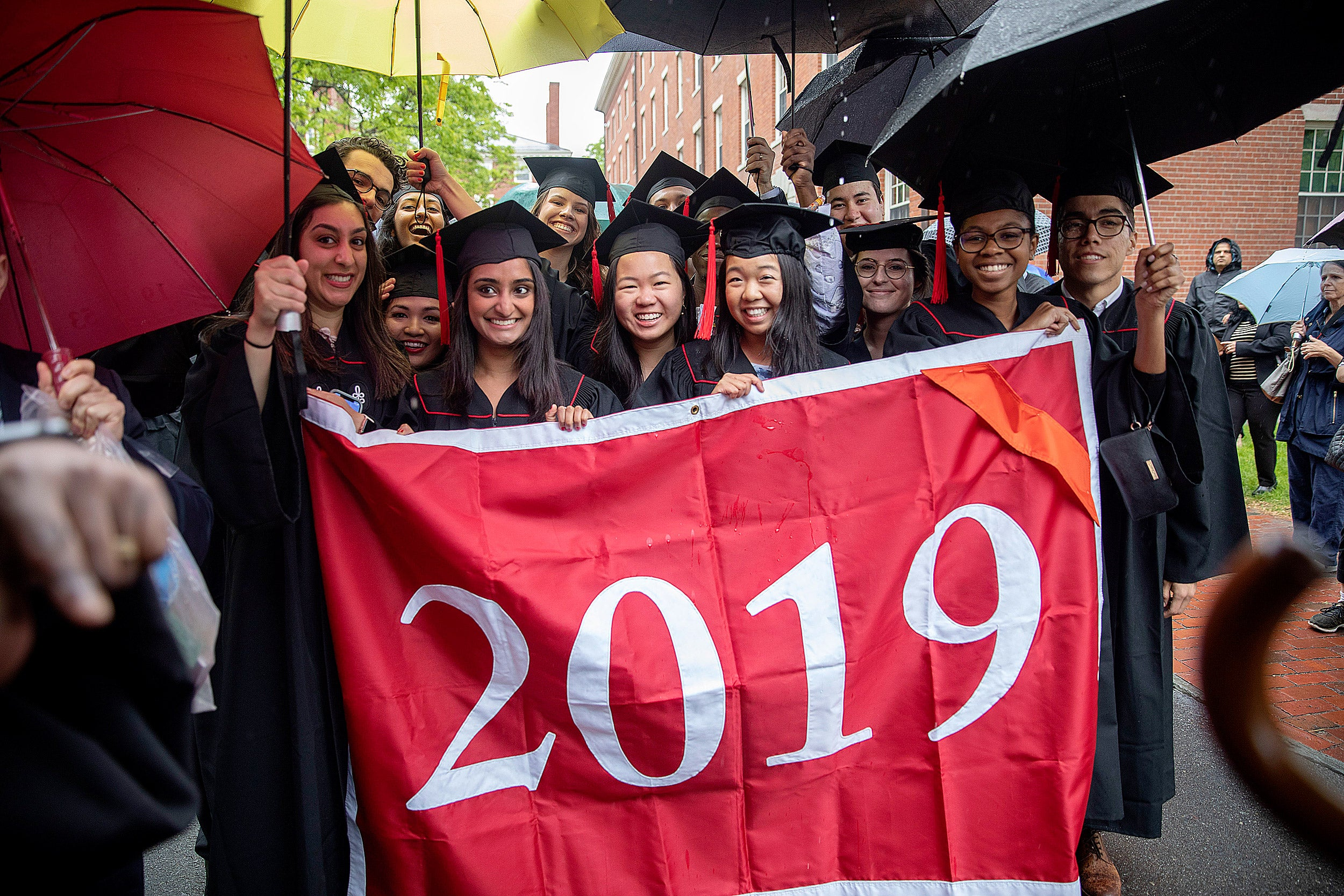 The Baccalaureate procession marches toward Memorial Church holding a 2019 banner and umbrellas.