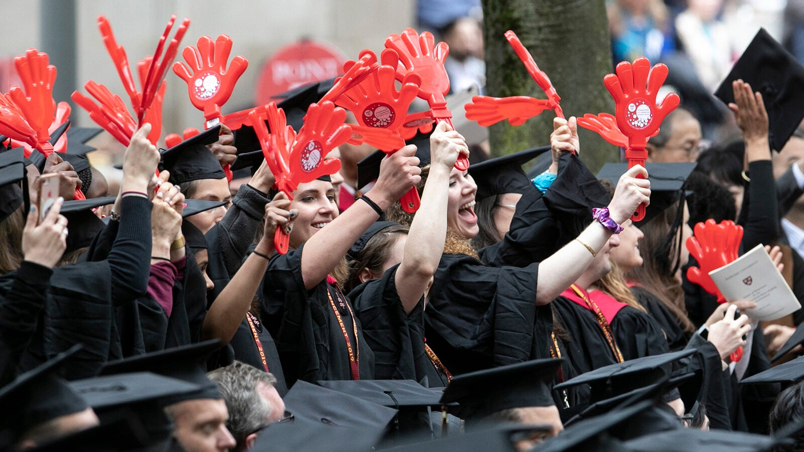 Harvard T.H. Chan School of Public Health graduates wave with red plastic clappers