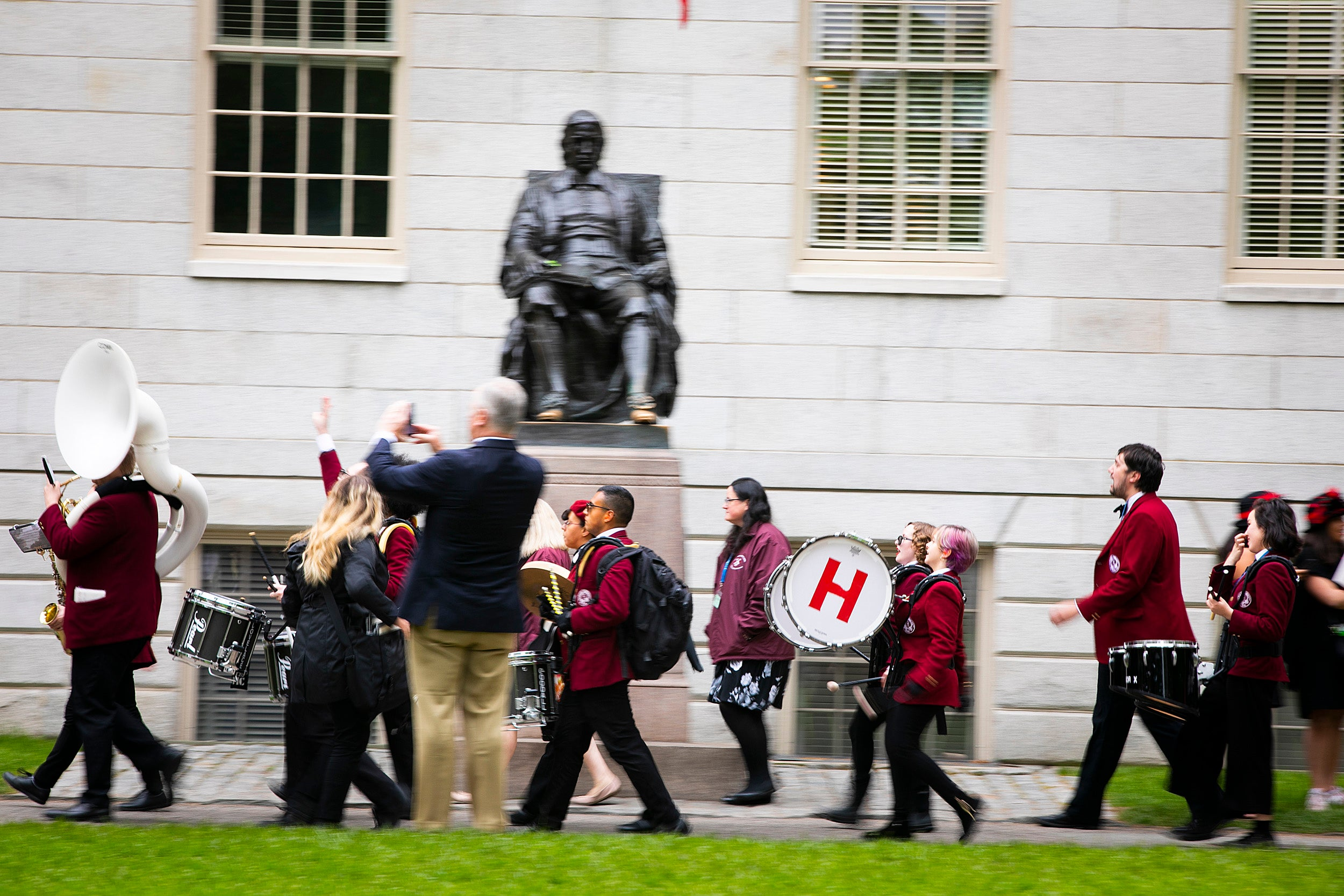 The Harvard Band marches by the John Harvard statues