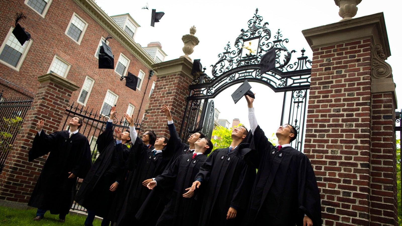 Graduates toss their caps in the air