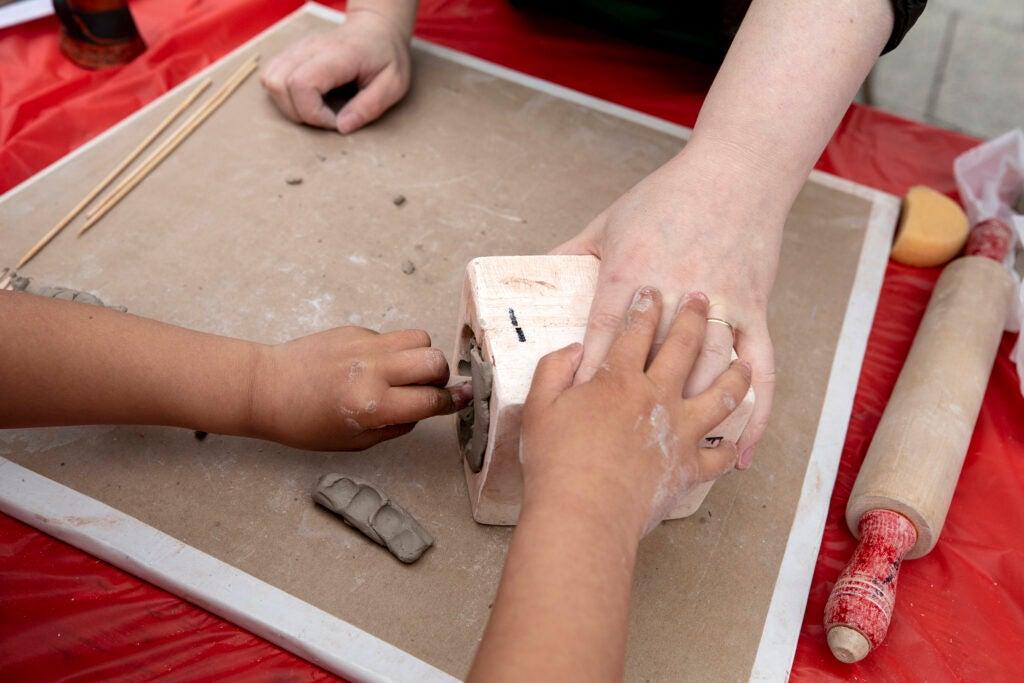 Child presses clay into a mold.