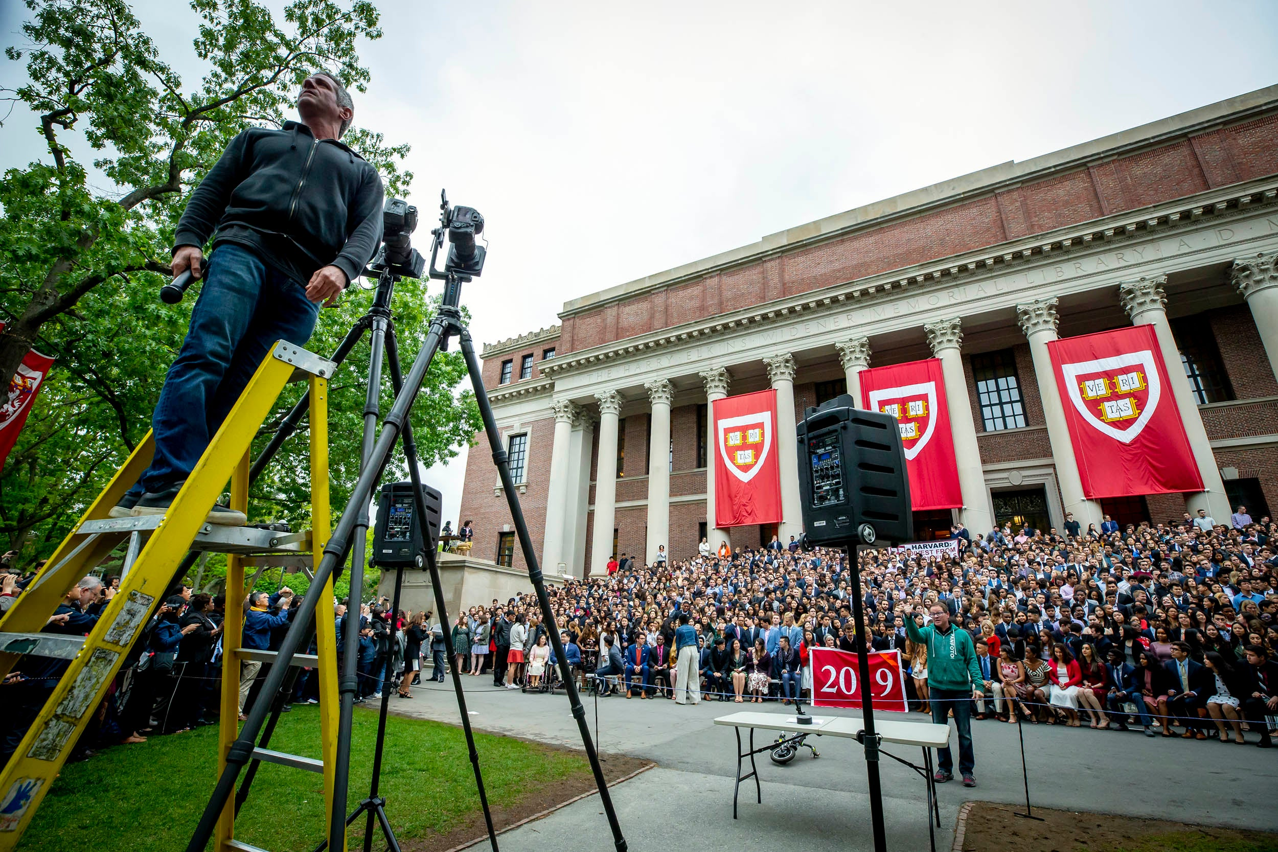 Photographer sets up class photo of graduates on the steps of Widener Library.