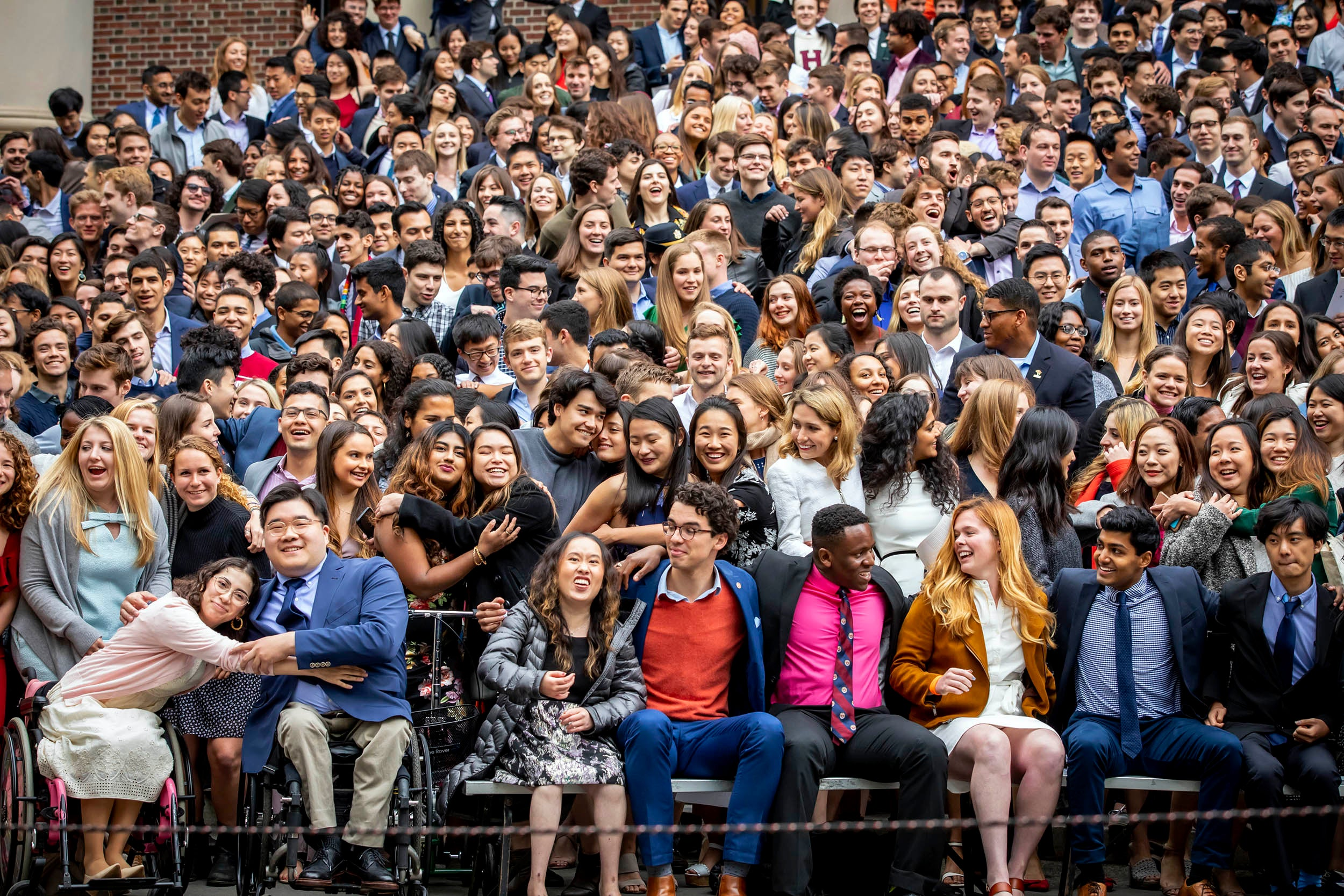 Seniors smile and hug on the steps of Widener Library.