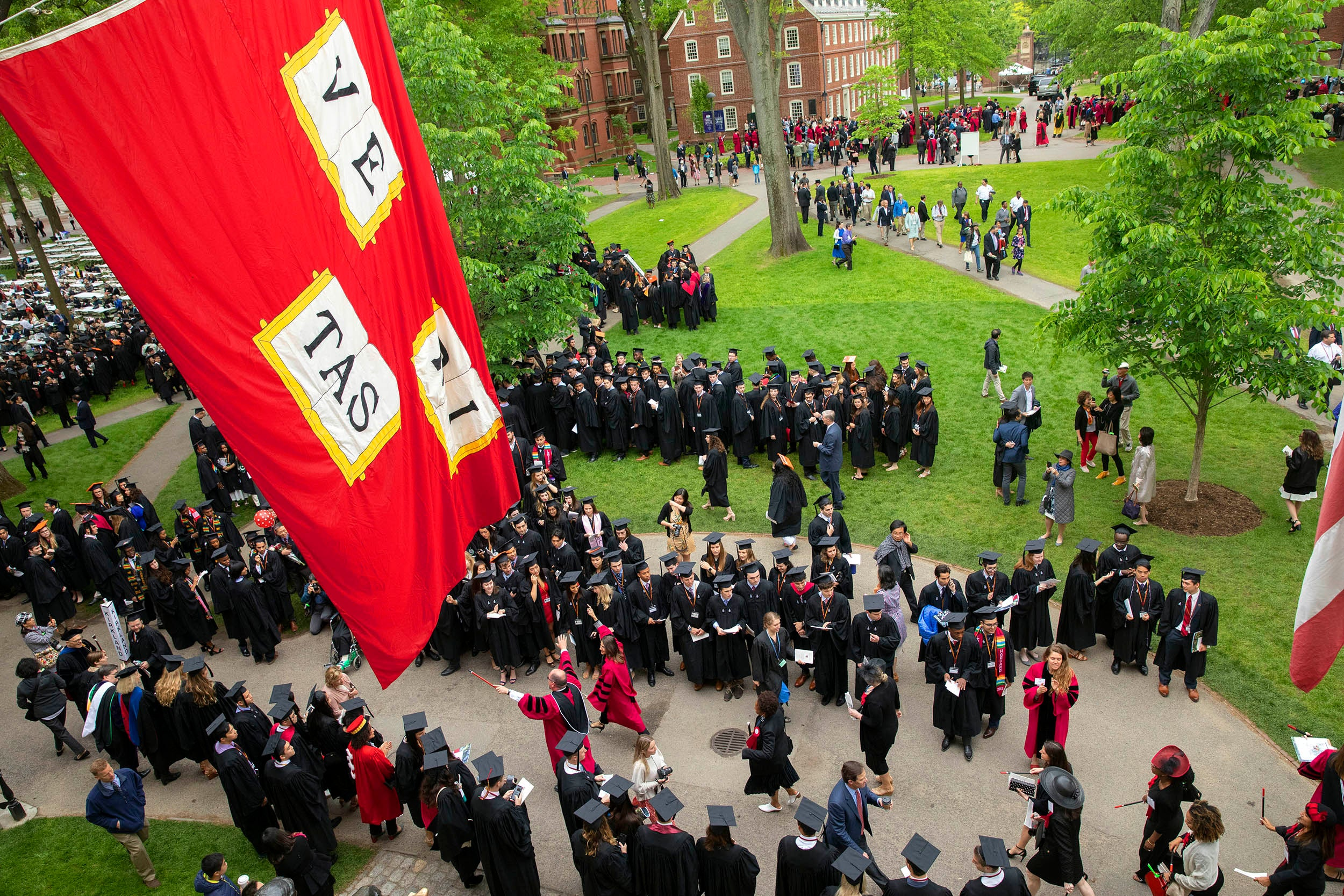 Seniors process past the John Harvard Statue and under the Veritas flag.
