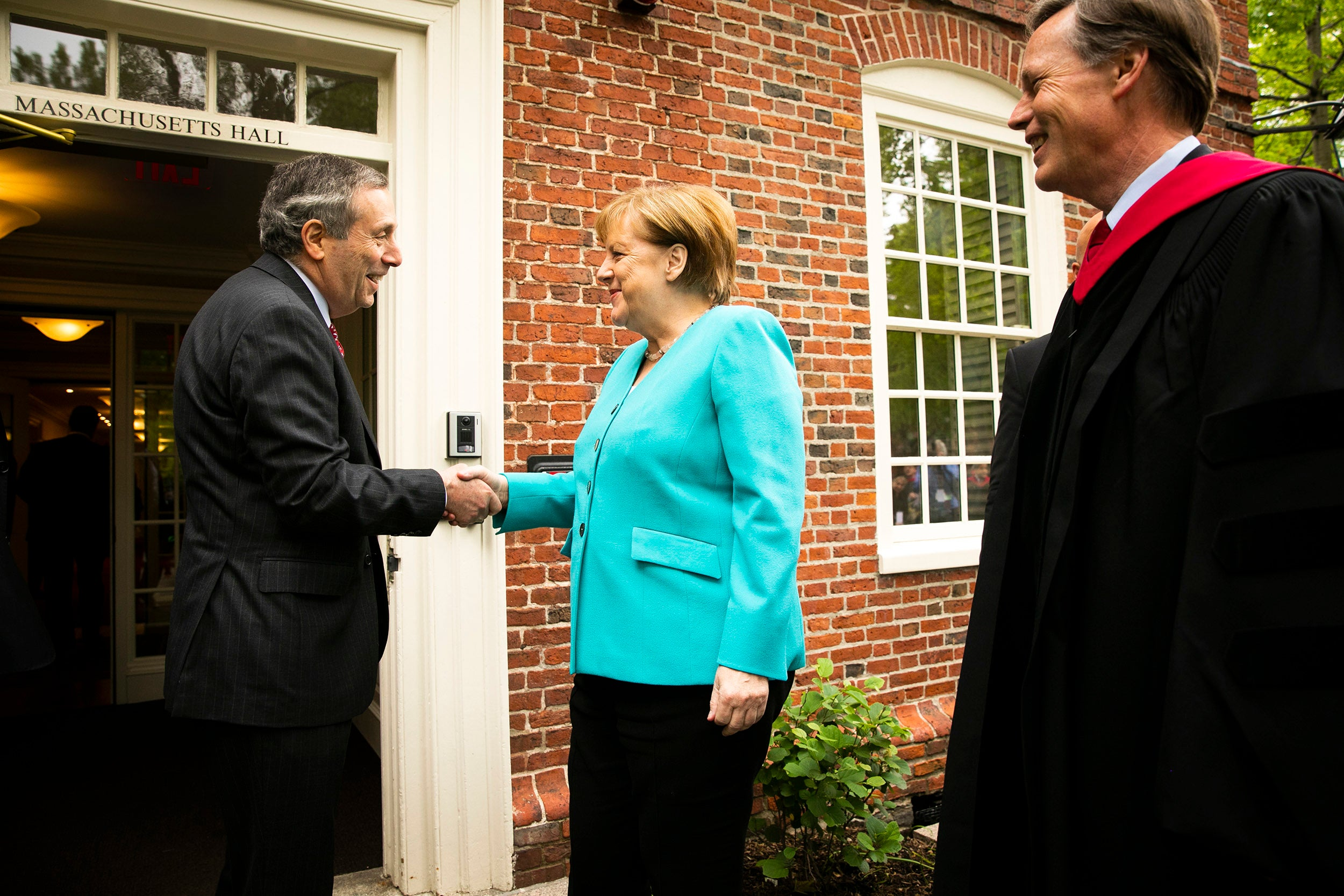 Larry Bacow shakes hands with Angela Merkel as Nick Burns looks on.