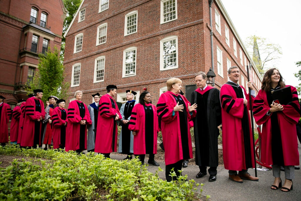 Honorary degree recipients and their escorts line up outside Massachusetts Hall.