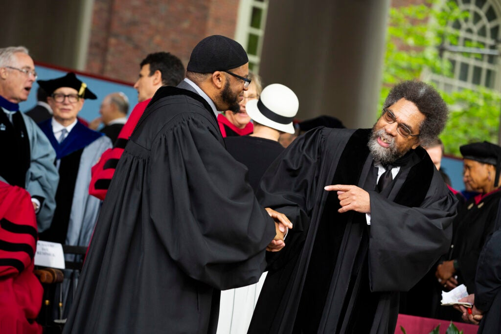 Khalil Abdur-Rashid and Cornel West shake hands on the stage.