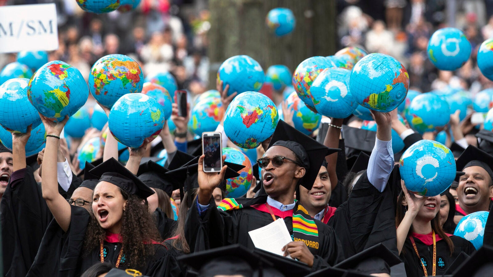 Kennedy School of Government graduates wave inflatable globes.