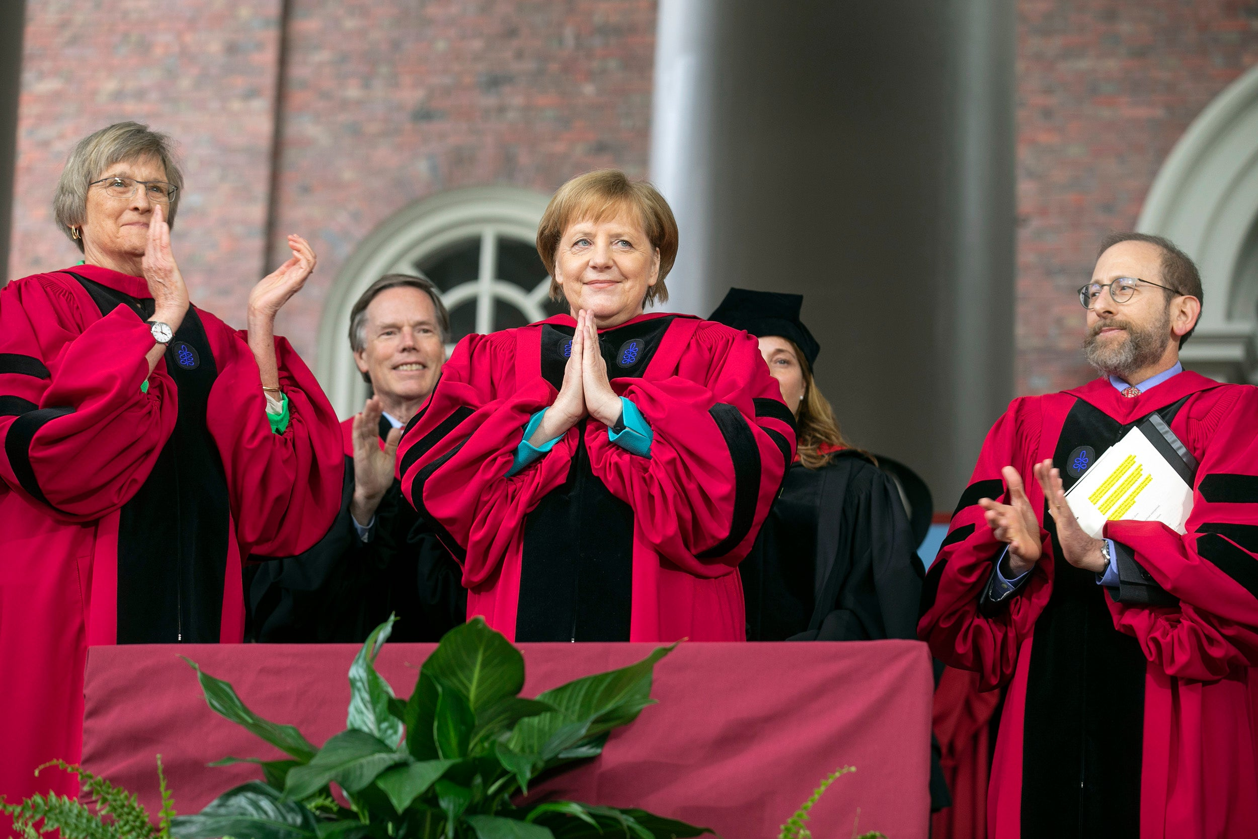Angela Merkel holds her hands in a prayer acknowledging the applause after receiving her honorary degree.