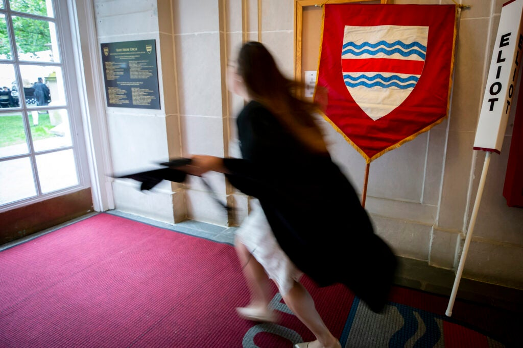 A students runs past an Elliot House shield on Commencement Day.