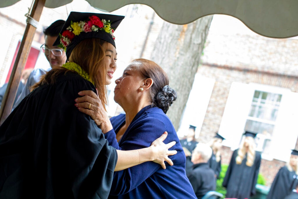 Moriah Lee hugs her grandmother Joleen Cordeiro who decorated her mortarboard with a lei.