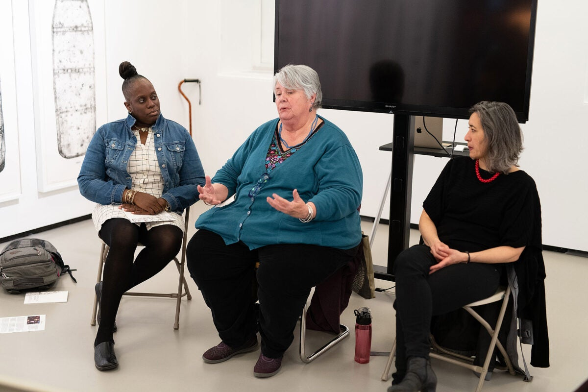 three women sitting in chairs, speaking to an audience