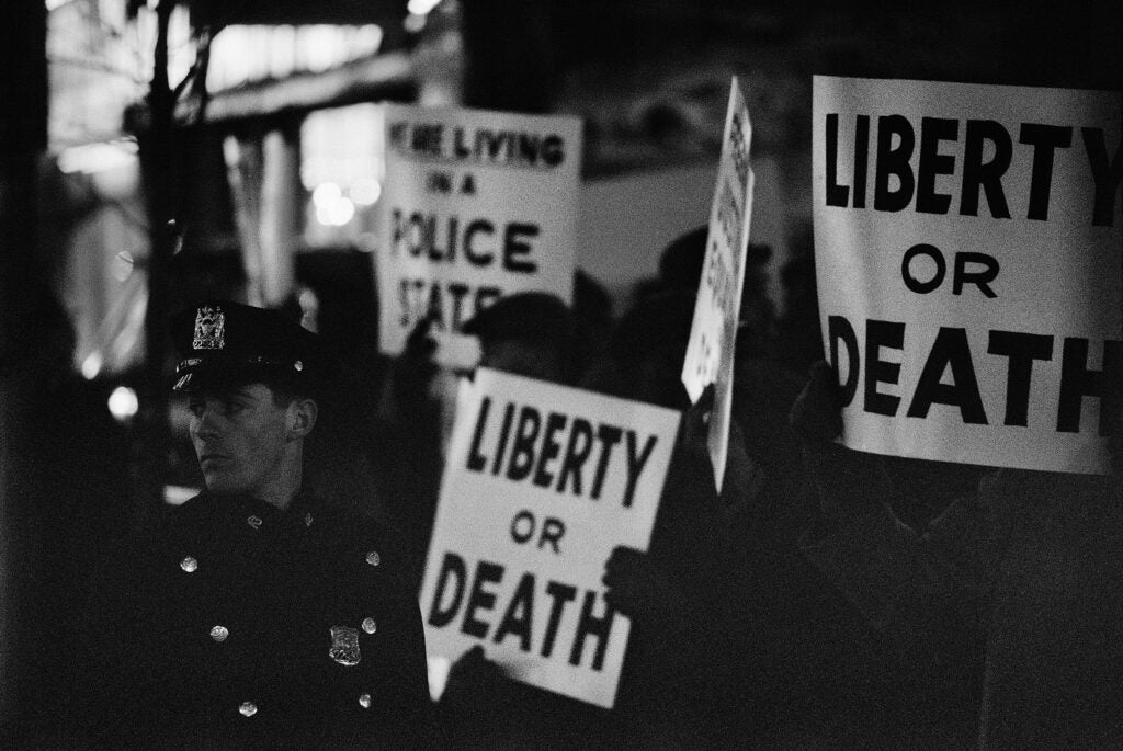 """""""Liberty or death"""" on posters in the background, a police officer in the foreground"""
