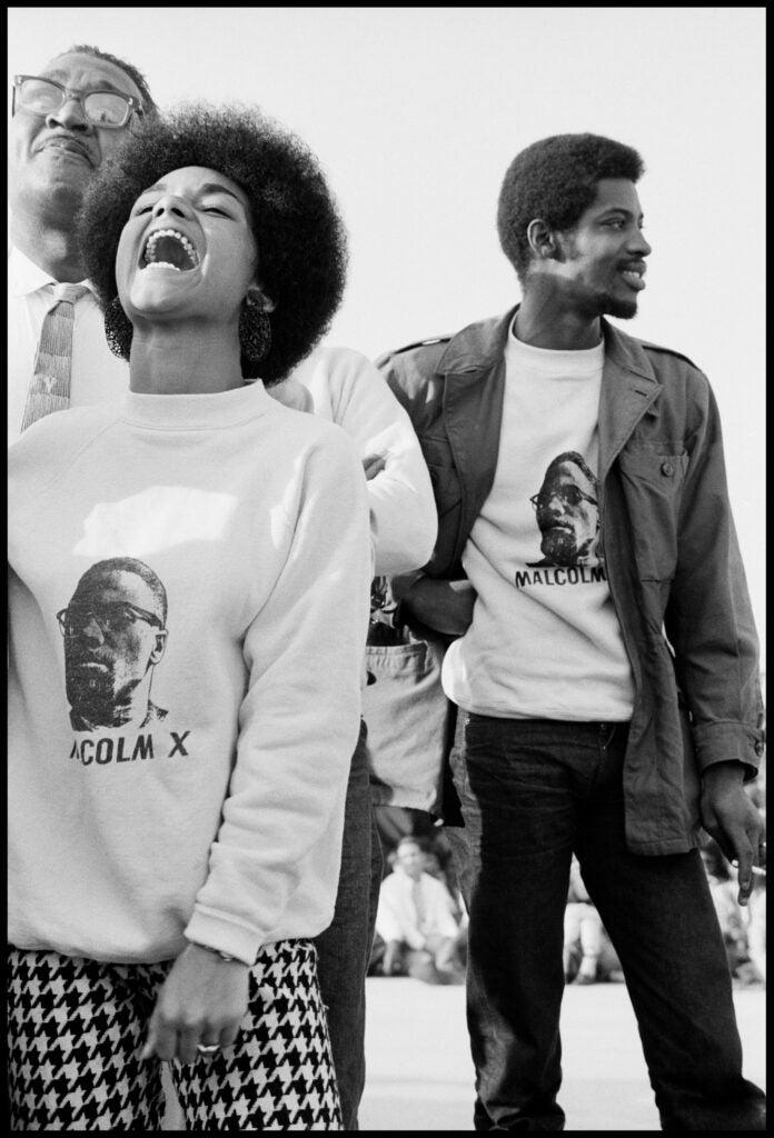 Three people wearing Malcolm X shirts