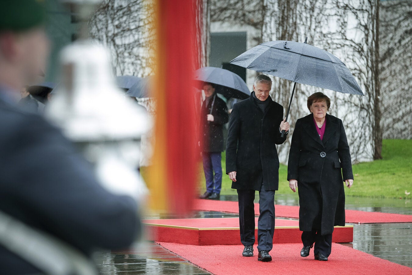 Angela Merkel walks under an umbrella with Krisjanis Karins, prime minister of Latvia.
