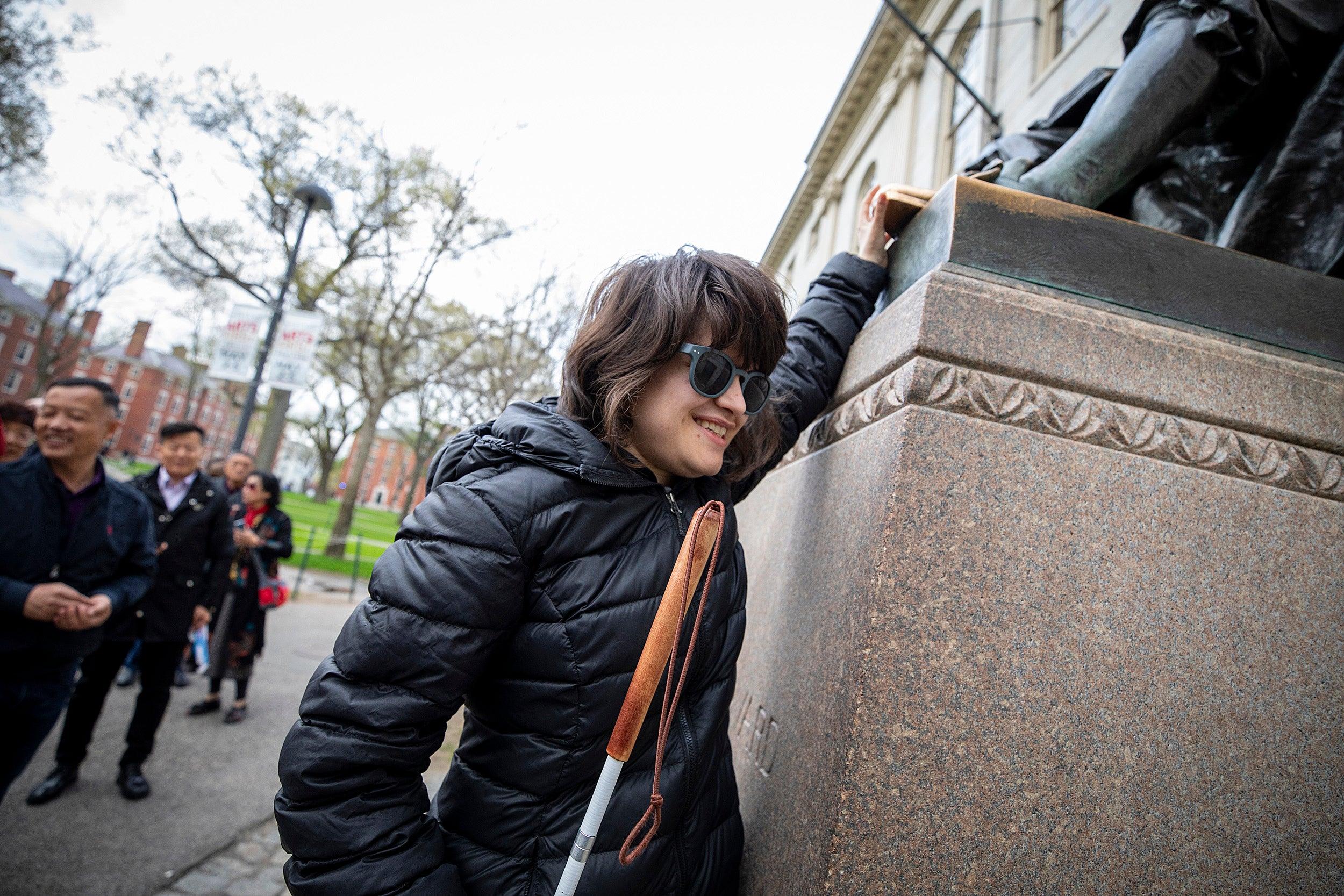 Jordan Scheffer touches the John Harvard statue.