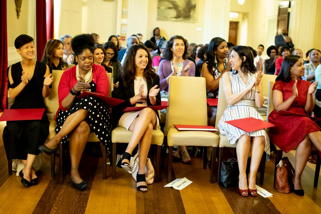 Harvard Fellows applaud during a ceremony