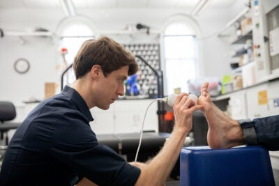 Nick Holowka, Postdoctoral Researcher, performs an ultra sound on callouses